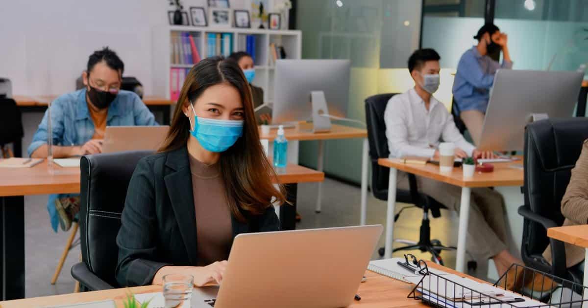 Désinfection des bureaux - Photo d'un open space avec 4 collaborateurs portant un masque devant leur ordinateur